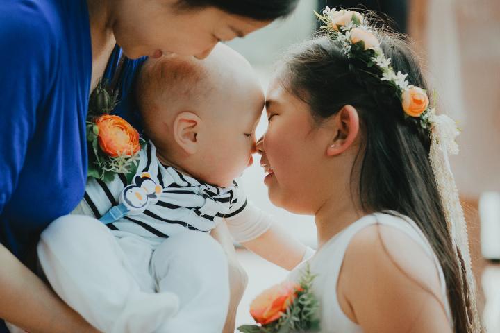 Flower girl kisses baby